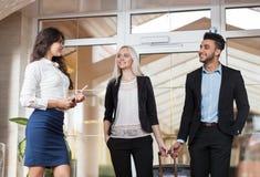 Пары дела гостеприимсва администратора гостиницы в лобби, человеке группы предпринимателей и гостях женщины приезжают Стоковые Изображения RF