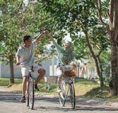 Пары держа руки пока езда велосипед стоковое фото
