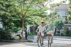 Пары держа руки пока езда велосипед стоковое изображение