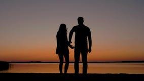 Пары держа руки приходя к пляжу и наслаждаясь заходом солнца на море сток-видео