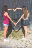 Пары девушек делая сердце сформировали тень с оружиями Стоковые Изображения RF