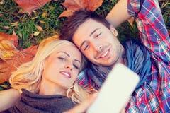 Пары лежа на листьях осени делают Selfie Стоковая Фотография RF