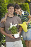 Пары держа моча чонсервную банку и цветочный горшок Стоковое Изображение RF