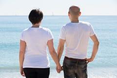 Пары держа один другого на пляже стоковое изображение rf