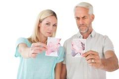 Пары держа 2 половины сорванного фотоснимка Стоковое фото RF