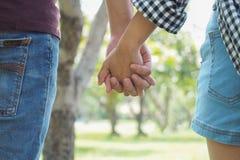 Пары держа руки в саде Стоковые Фото