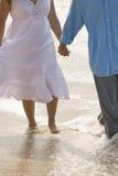 Пары держа руки идя на пляж Стоковые Фотографии RF