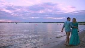 Пары держа руки на заходе солнца пляжа на перемещении каникул медового месяца Счастливые романтичные молодые любовники, человек и видеоматериал