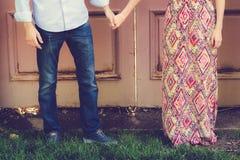 Пары держа руки перед античной дверью Стоковая Фотография
