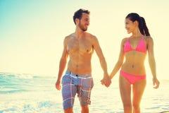 Пары держа руки совместно на заходе солнца пляжа Стоковое Изображение RF