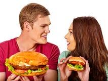 Пары есть быстро-приготовленное питание Человек и женщина едят гамбургер с ветчиной Стоковое Изображение