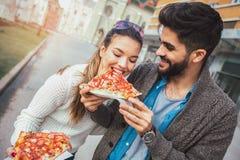 Пары есть пиццу outdoors и усмехаться Стоковое Изображение