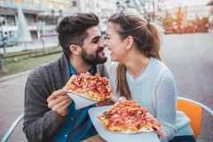 Пары есть пиццу outdoors и усмехаться Стоковые Изображения