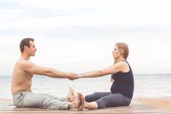 Пары делают протягивать на побережье Стоковые Фото