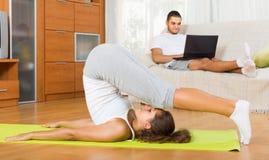 Пары делая йогу с компьтер-книжкой Стоковые Фото