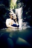 Пары делая обнимать под водопадом Стоковая Фотография