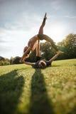 Пары делая циркаческую йогу на траве Стоковая Фотография
