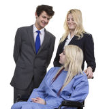 Пары дела смотря женщин сидя на кресло-коляске Стоковая Фотография