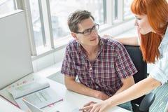 Пары дела смотря один другого пока использующ компьтер-книжку в творческом офисе Стоковая Фотография RF
