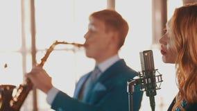 Пары джаза выполняют в ресторане Стиль саксофониста вокалиста ретро музыканты акции видеоматериалы