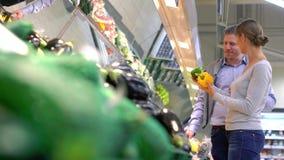 Пары женщины и человека покупая свежие фрукты в супермаркете акции видеоматериалы