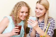 Пары женщин смотря телефон в кафе Стоковая Фотография RF