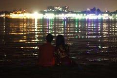 Пары запятнали сидеть совместно и наслаждаться светами стоковые изображения