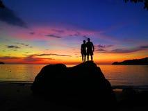 Пары зашкурить на утесе перед заходом солнца стоковое фото