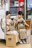 Пары зрелых дам в традиционных японских одеждах сидя в метро токио, Японии стоковые фото