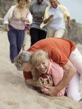 Пары играя американский футбол на пляже Стоковые Изображения