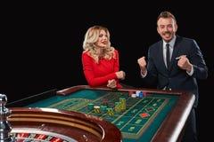 Пары играя выигрыши рулетки на казино Стоковая Фотография RF