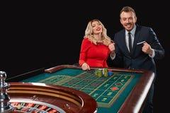 Пары играя выигрыши рулетки на казино Стоковое фото RF