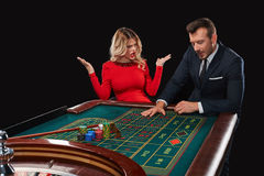 Пары играя выигрыши рулетки на казино Стоковые Изображения