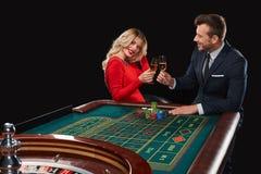 Пары играя выигрыши рулетки на казино Стоковое Изображение