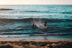 Пары играя на пляже на скалах захода солнца, Сан-Диего стоковое фото rf