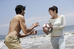 Пары играя с футболом на пляже Стоковые Фотографии RF