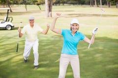 Пары игрока в гольф празднуя успех пока стоящ на поле Стоковые Фотографии RF