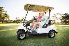Пары игрока в гольф сидя в багги гольфа Стоковое Изображение