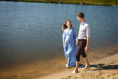 Пары идя на воду вдоль берега реки держа руки совместно Стоковая Фотография RF