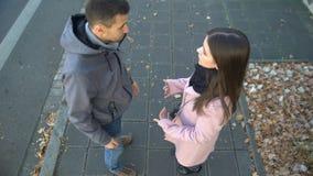 Пары идя на спорить улицы, женщина нажимая человека и идя прочь, прекращают сток-видео