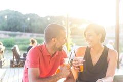 Пары имея коктеиль внешний на заходе солнца Стоковые Изображения RF