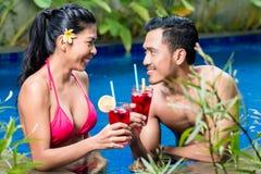 Пары имея пить в бассейне в Азии стоковое фото rf