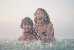 Пары имея потеху в море стоковая фотография rf