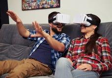 Пары имея потеху используя белые стекла виртуальной реальности Стоковые Фото