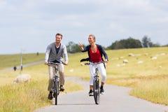 Пары имея путешествие велосипеда морского побережья на дамбе Стоковое фото RF