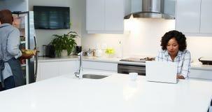 Пары используя компьтер-книжку в кухне 4k сток-видео