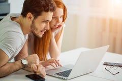 Пары используя компьтер-книжку на столе дома и думают Стоковое Фото