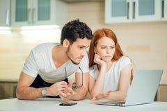 Пары используя компьтер-книжку на столе дома и думают Стоковые Изображения