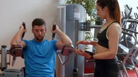 Пары используя машину весов в спортзале сток-видео