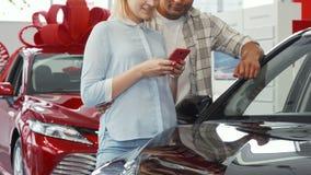 Пары используя умный телефон пока покупающ новый автомобиль стоковое изображение